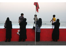 Maldivian women and their children by the bright red sea wall