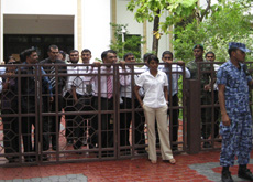 MPs watch the protests from behind the gates of the Majlis