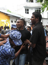 Police restrain protesters outside parliament