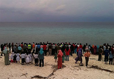 A crowd gathers on the beach of Fuahmulah for the arrival of rower Guin Batten.