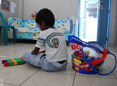 A child plays with a toy at Vilingili orphanage